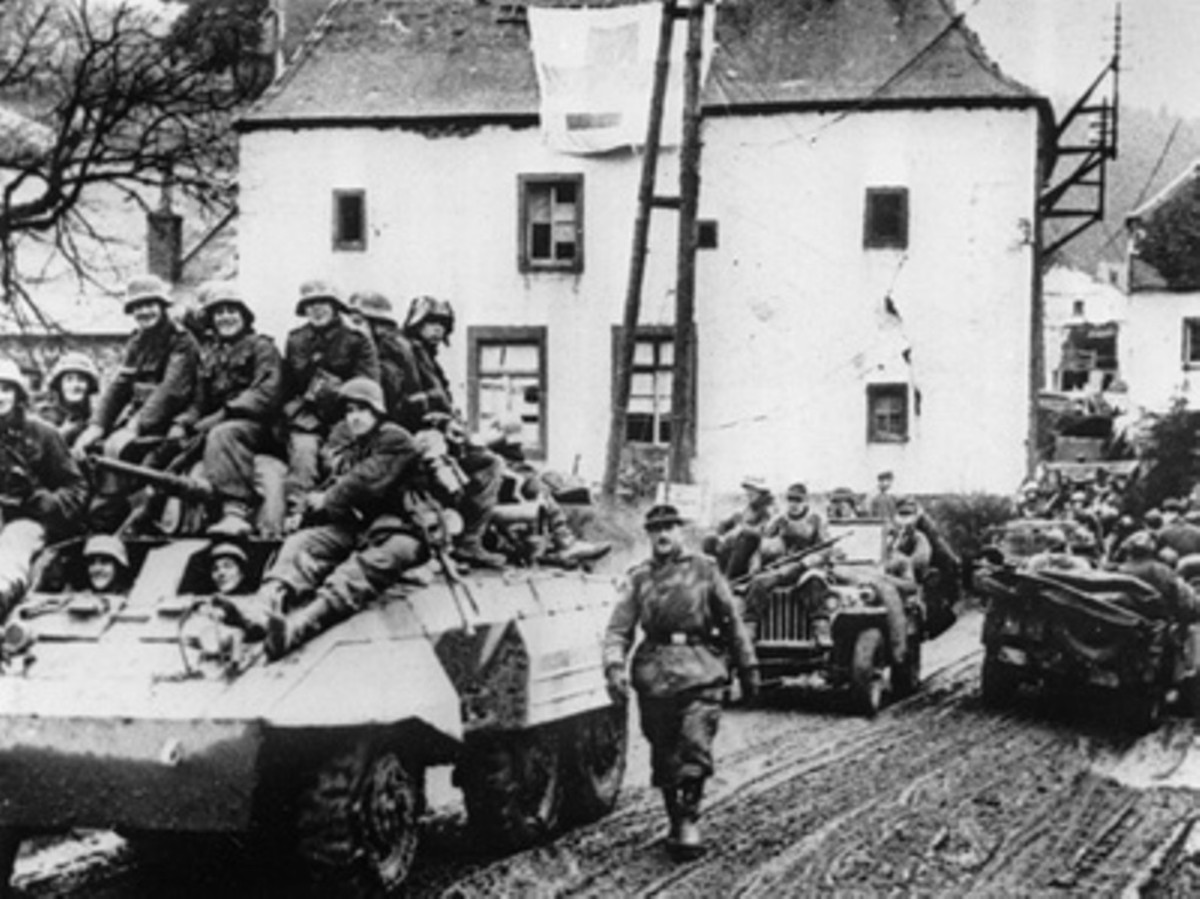 Germans troops moving west in captured American vehicles on Dec 16-17. In front is an M8 Greyhound and a jeep next in line. I believe this village to be Honsfeld.