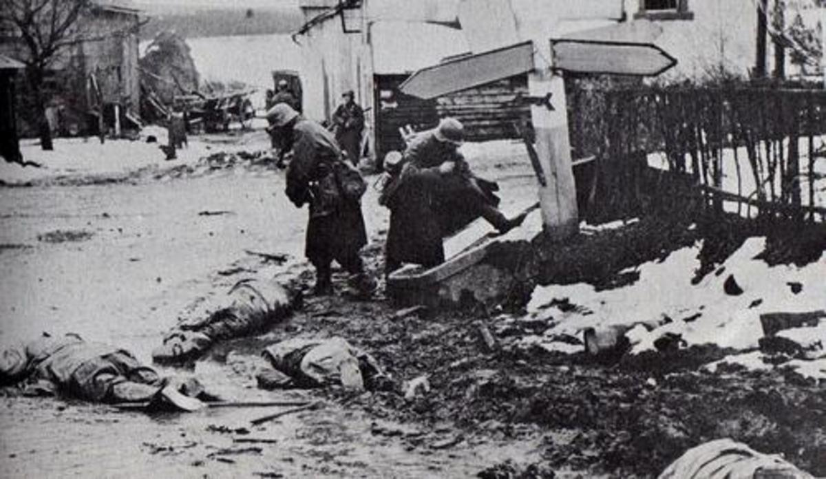 German soldiers stealing dead GI's boots in the village of Honsfeld. The road signs have been blocked out by the censors.
