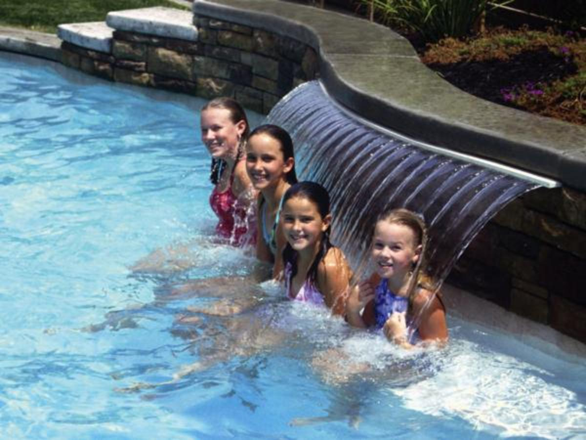 four children in a swimming pool with fountain behind them massaging their necks and upper backs