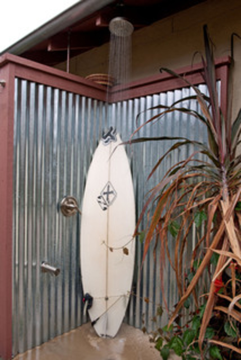 outdoor swimming pool shower with metal corrugated walls and a surf board