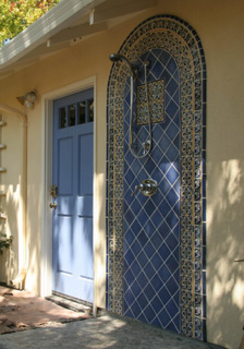 classic blue tile in arch design for an outdoor shower near a swimming pool