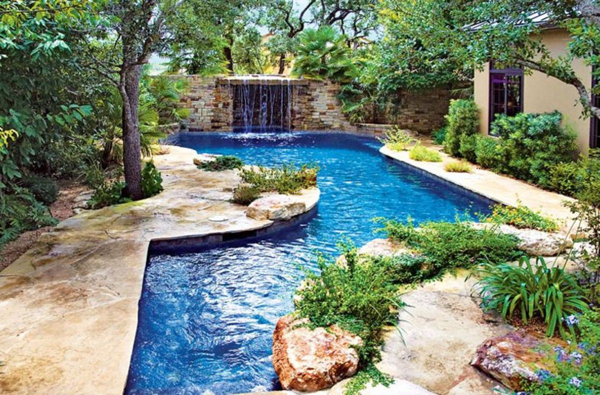 beautiful swimming pool with water fountain grotto, decorative patio and landscaping