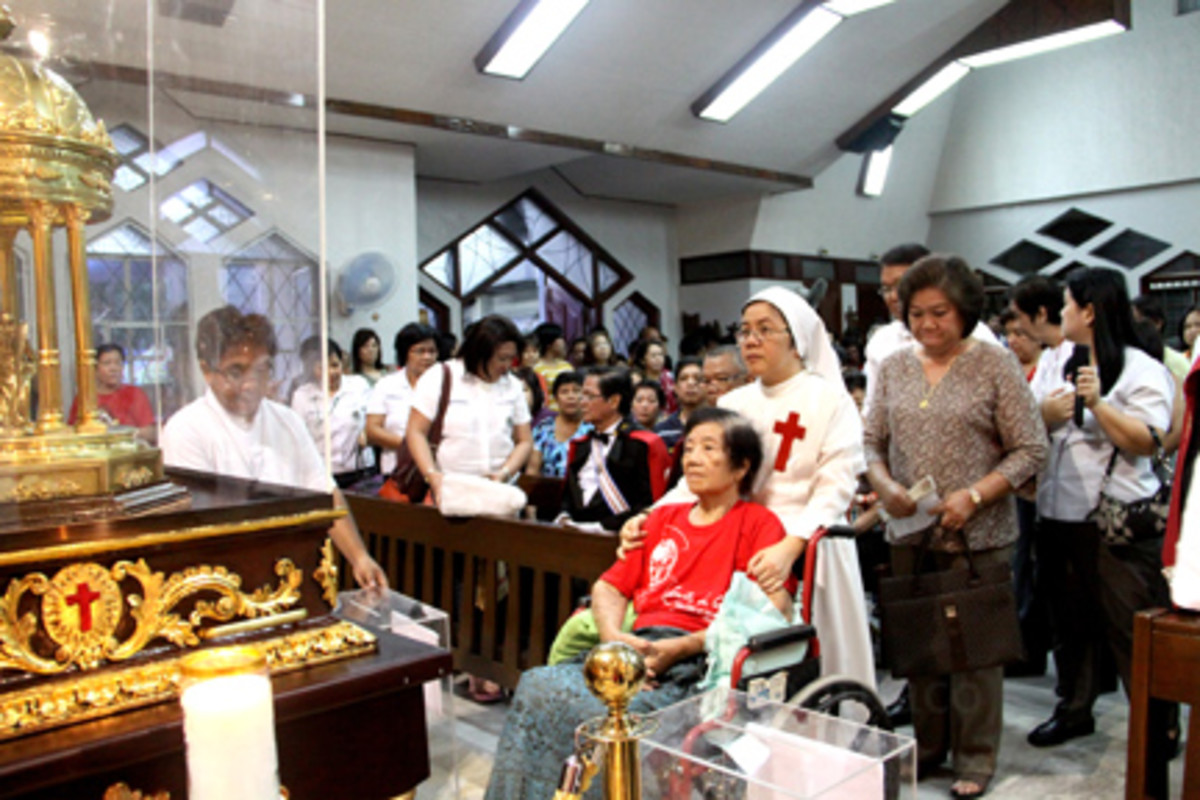 a disabled being assisted by a Camillian sister during the relic visit