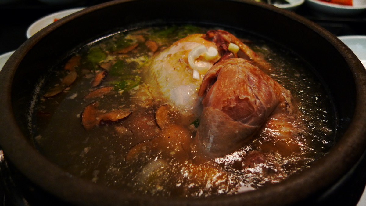 chicken ginseng soup. a whole young chicken is stuffed with rice and boiled in a broth of Korean ginseng, dried seeded jujubes, garlic and ginger.