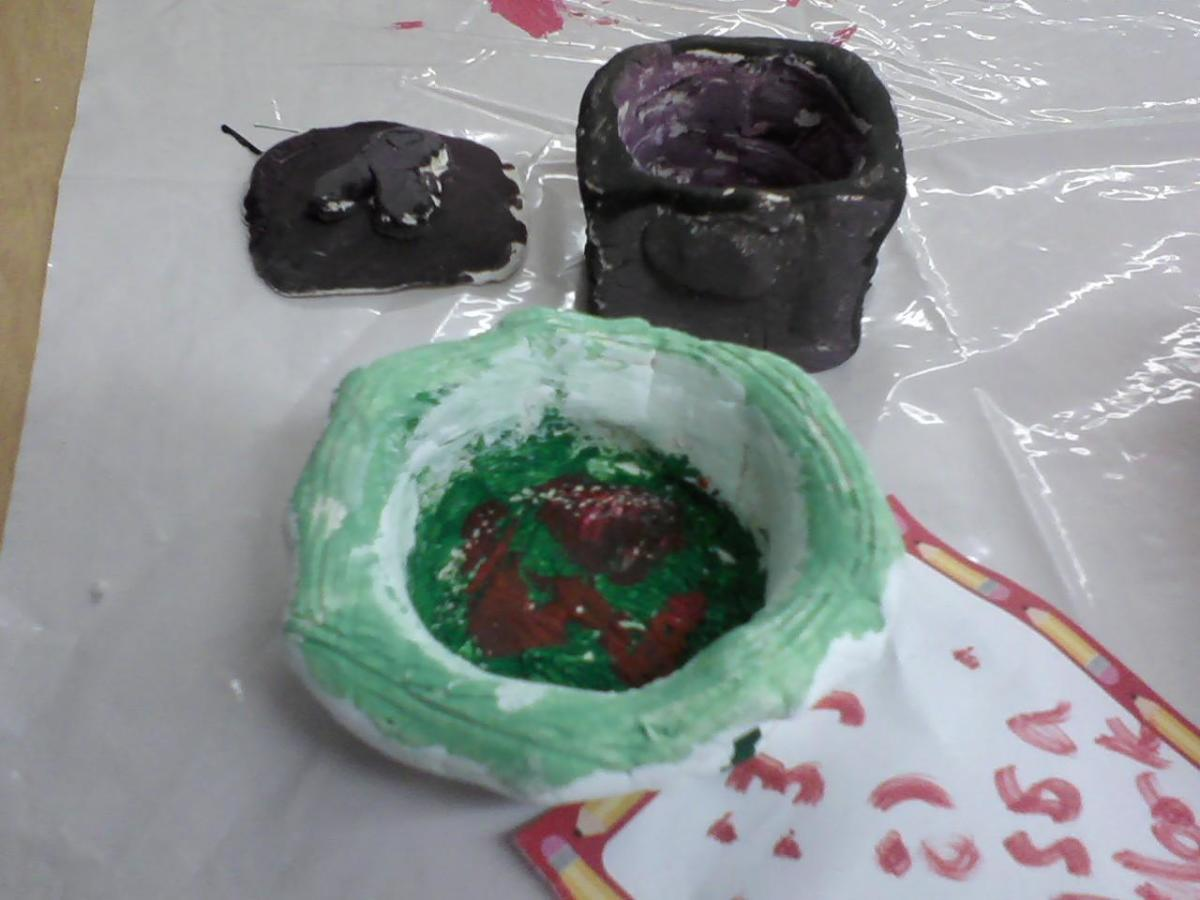 A 4th grader's painted pinch pots, one small dish, lid and bowl