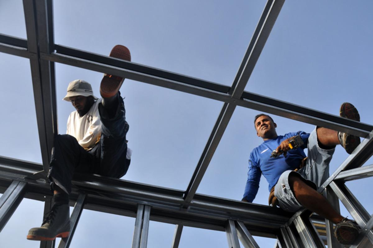 Los roofmen en el trabajo que se fijan los marcos firmemente a la base.