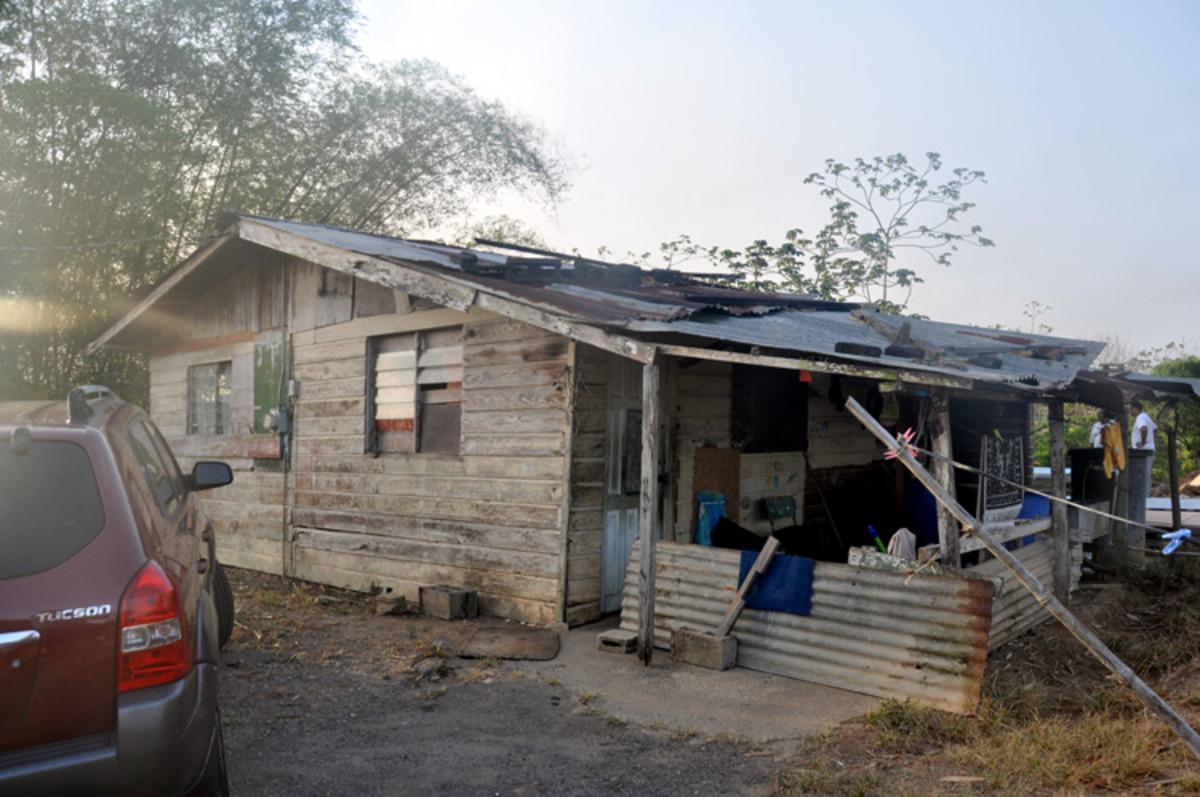 Con muchas goteras en el techo y las paredes débiles, esto apenas podía llamarse una casa.  Ver a la gente en el fondo la topografía de un posible sitio de construcción.