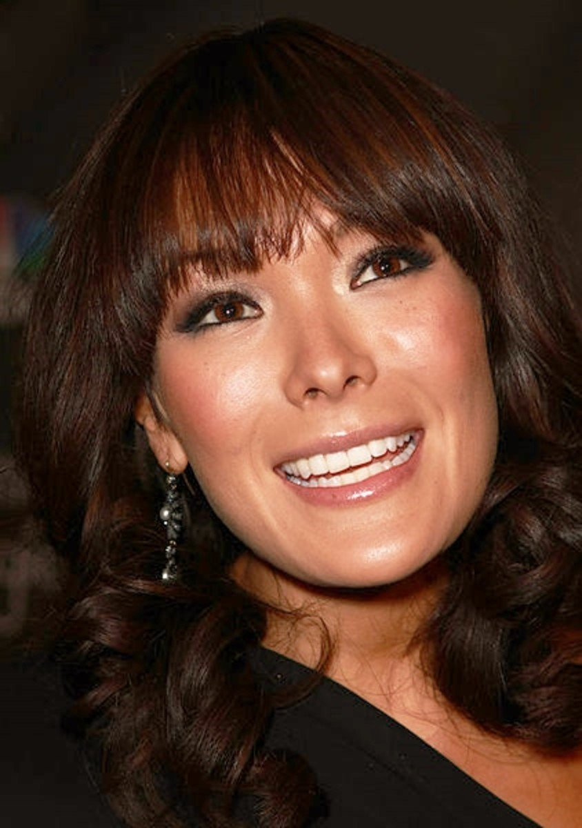 Lindsay Price with a short curly hairdo with bangs