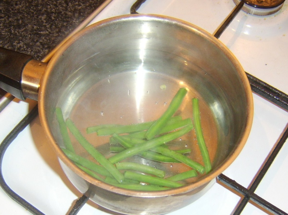 Trimmed grean beans are blanched in simmering, salted water