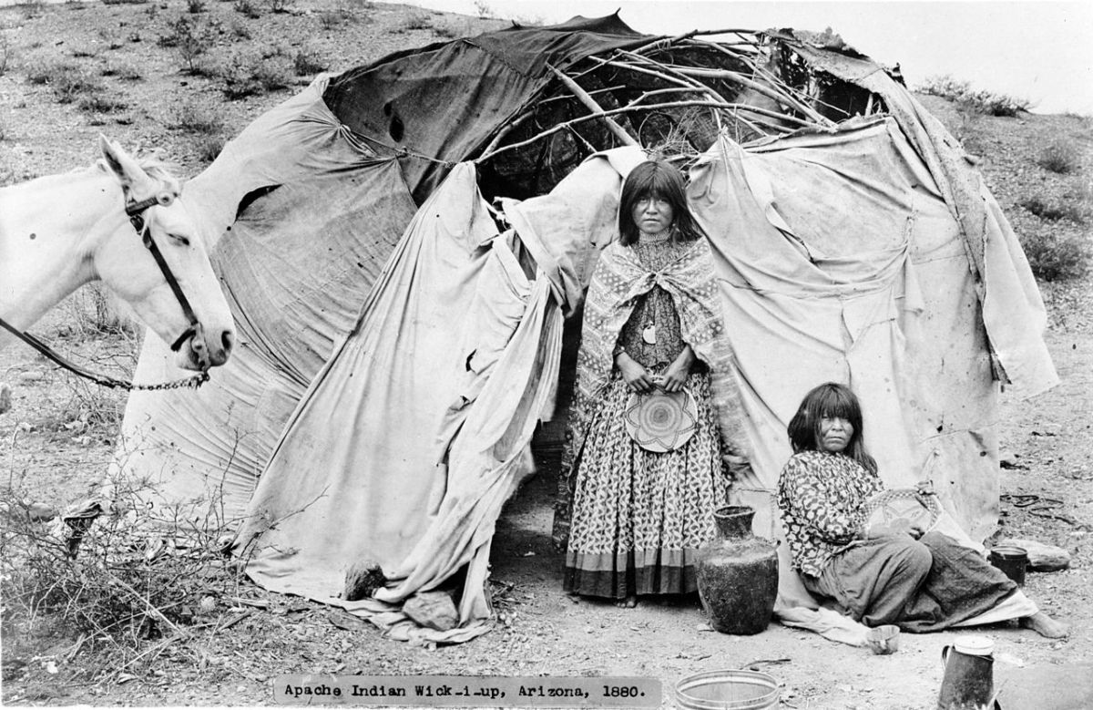 Apache women outside their cloth covered wickiups in a camp in Arizona. 1880