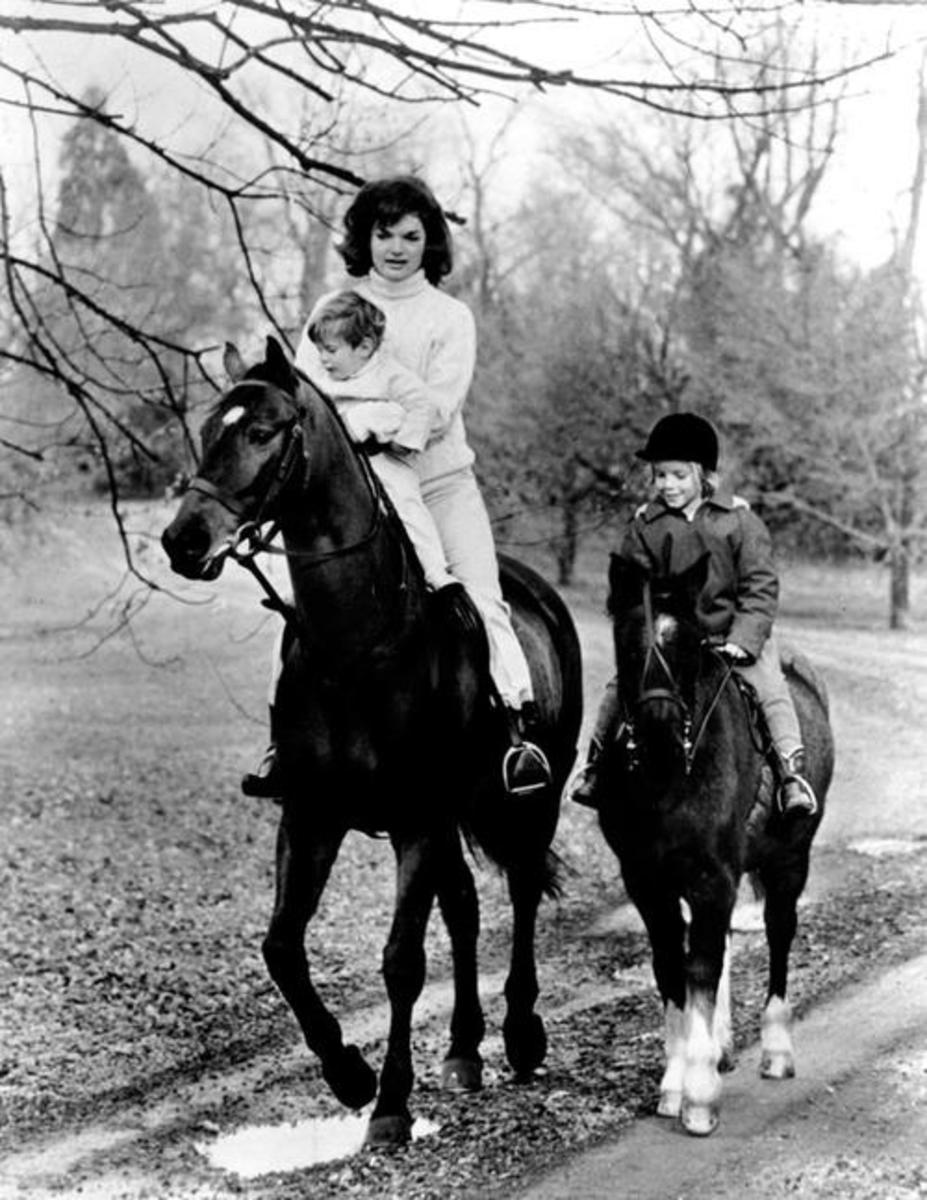 First Lady Jacqueline Kennedy and her children John F. Kennedy Jr. and Caroline Kennedy riding. Photograph distributed by the White House for the children's birthdays, 1962.
