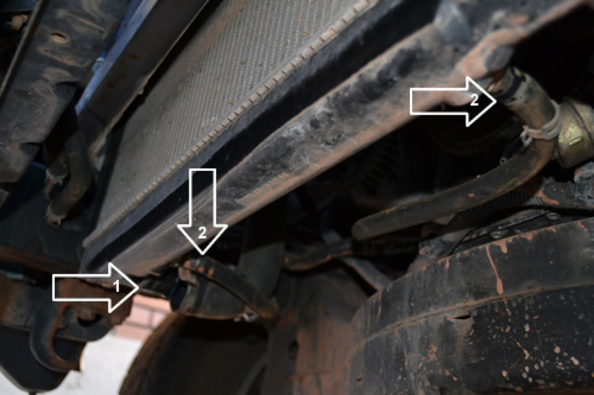 Disconnect the 1) Lower radiator hose and 2) both of the Automatic Transmission (A/T) cooler hoses