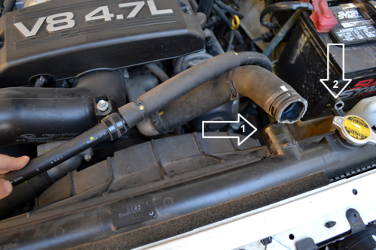 Disconnect the 1) Upper radiator hose and 2) Radiator reservoir hose
