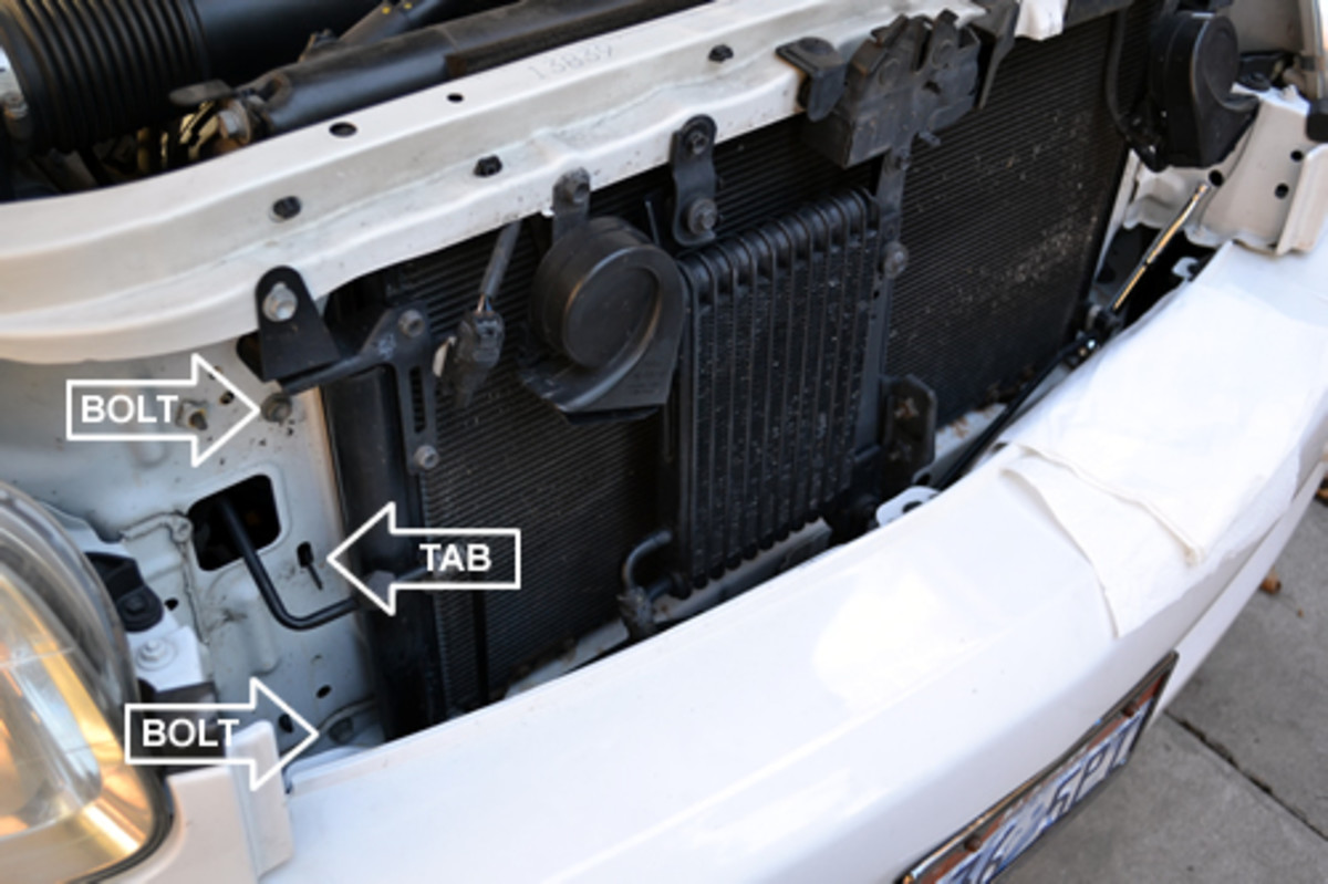 Remove the bolts holding the radiator in, there are 4 total with 2 on each side (only 2 are visible in this photo).  The Tabs will hold the radiator in place even when the bolts are removed.