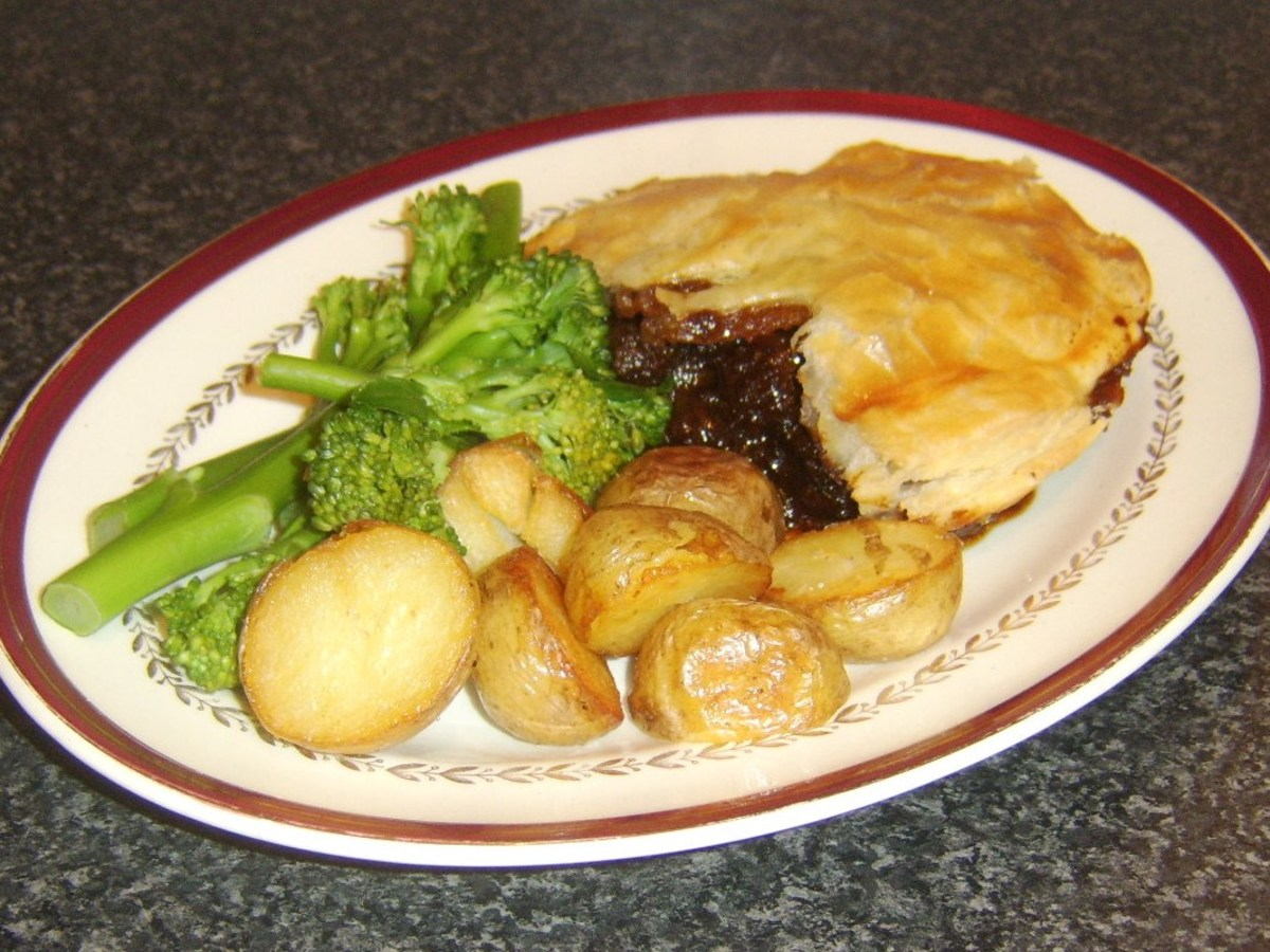 Pork and venison in red wine and rowan gravy pie is served with roast potatoes and broccoli