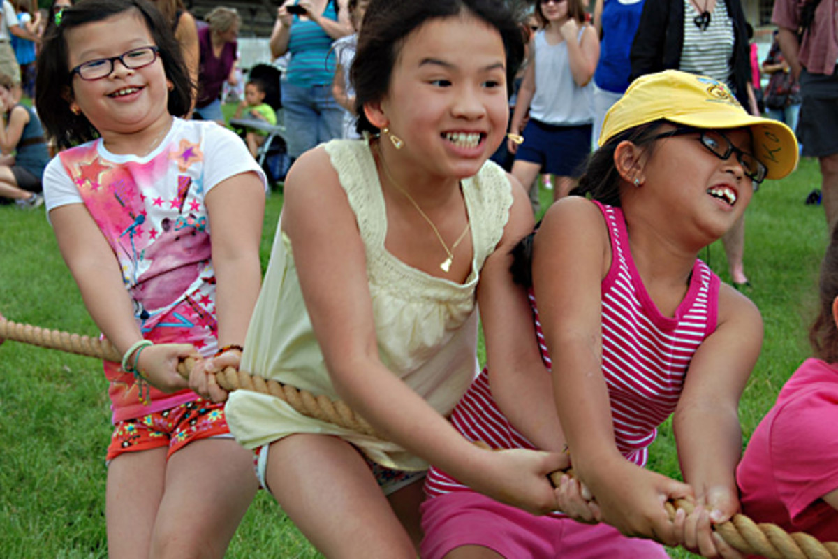 Young children enjoy a fun tug of war at an event in the Sky Meadows State Park in Virginia USA