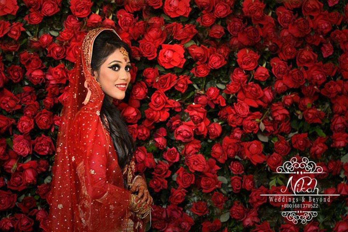 A gorgeous La Belle Bride in red with a backdrop of lush red roses.