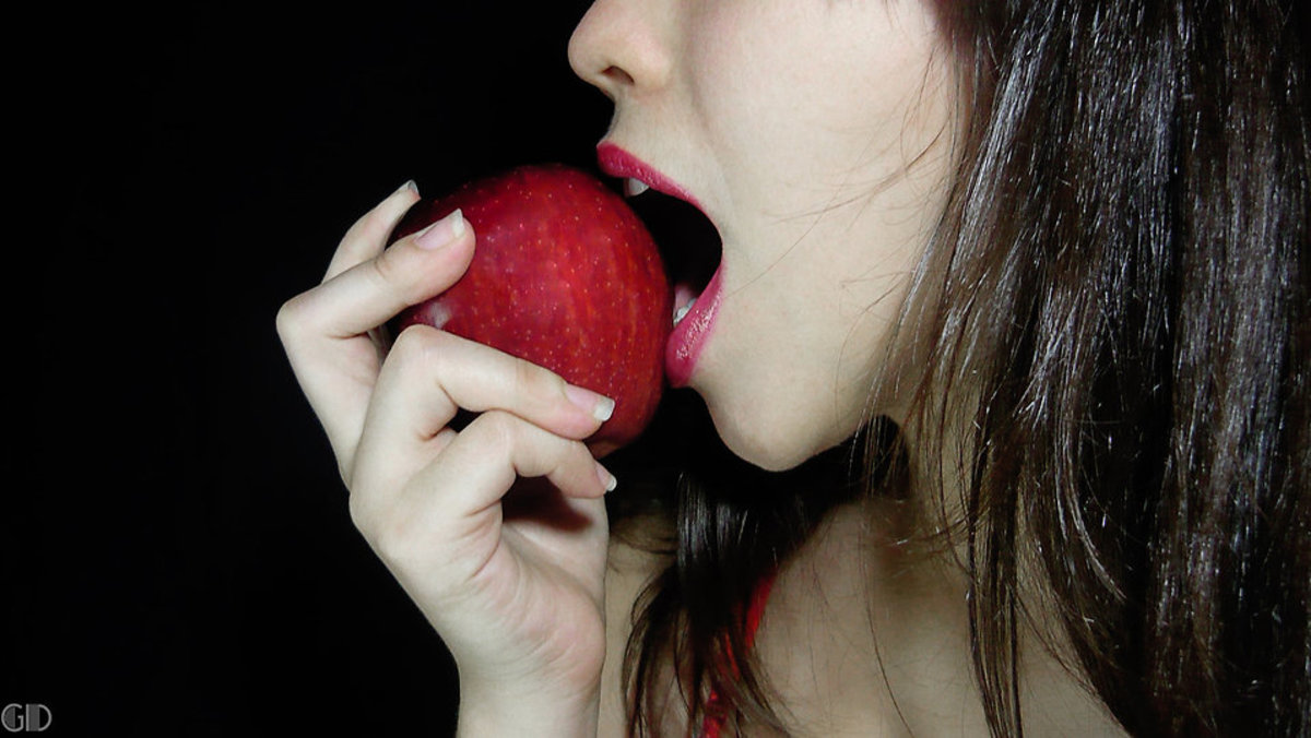 Beautiful girl eating a raw red apple