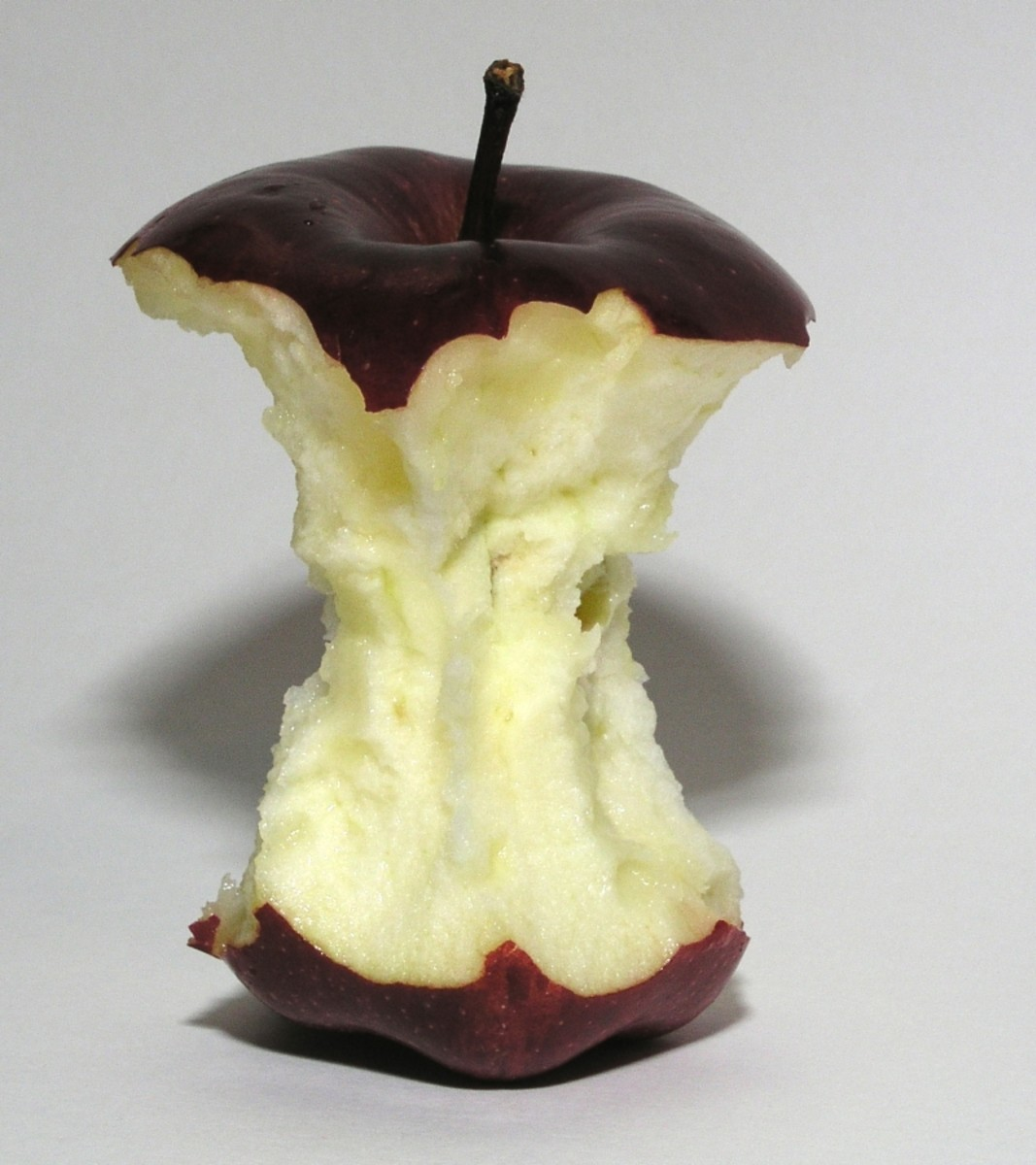 The remaining of a red apple that has been mostly eaten.
