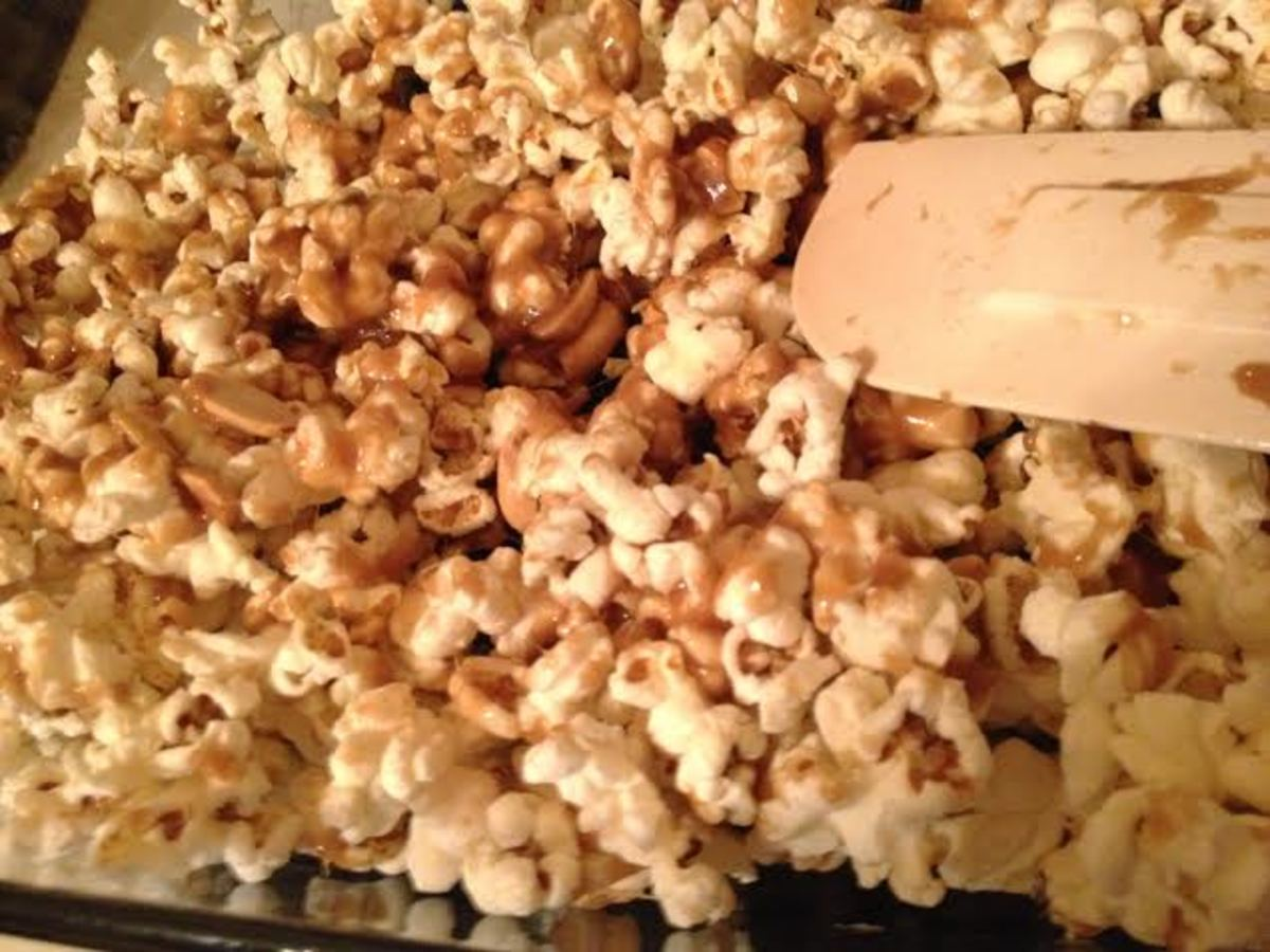 Stir the caramel and the popcorn to start the coating process.