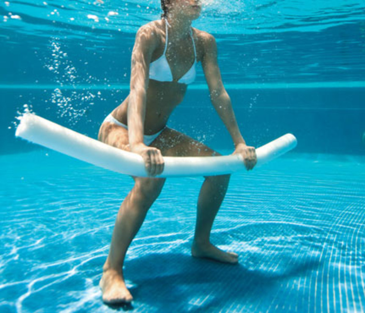 women exercising with a white pool noodle underwater in a white bikini