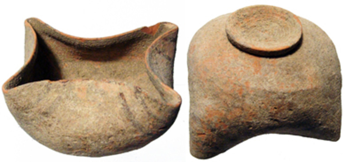 Indus Valley, Nal Culture of Baluchistan, 2900 - 2500 BC. The terracotta oil lamp. The body rounded with raised disk foot, the corners pinched to form spouts, brown line decoration on each. Intact with earthen encrustation