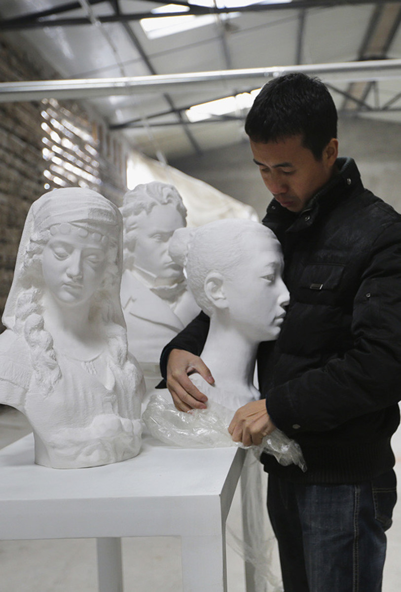 Li Hongbo with a few of his busts.