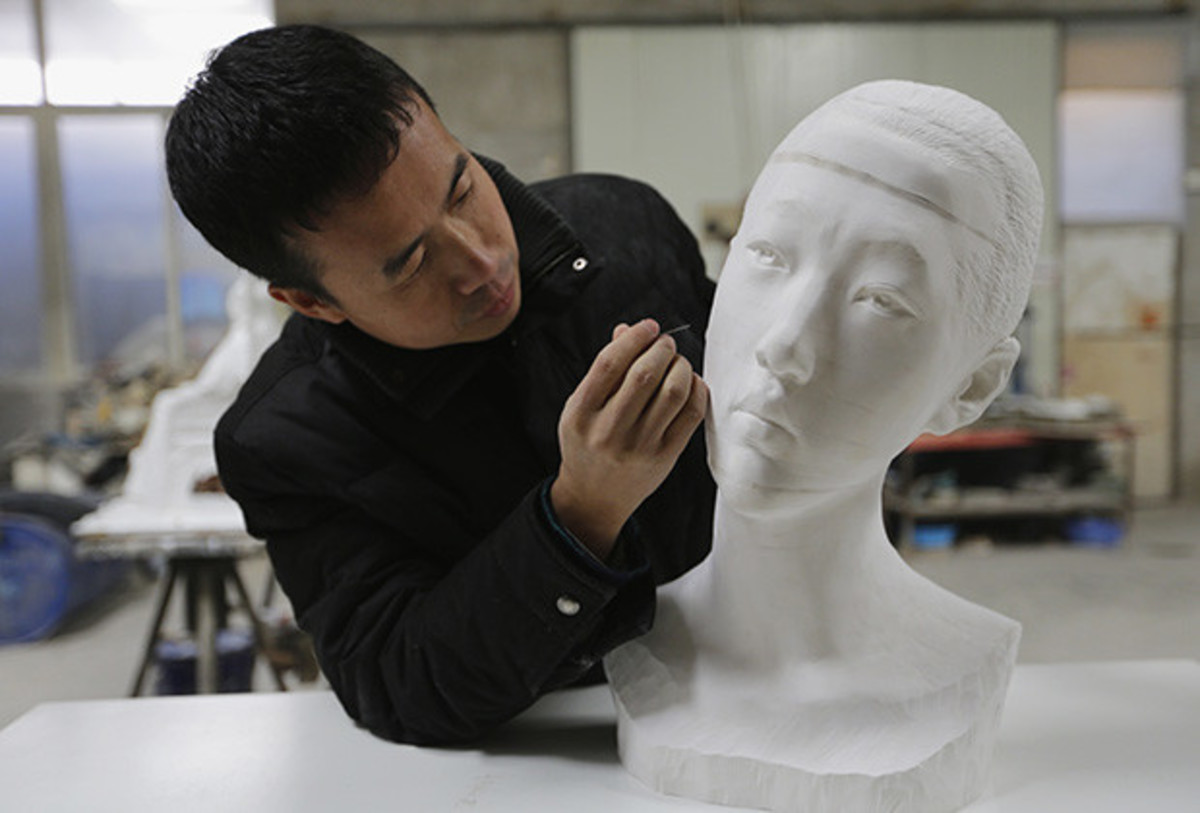 Li Hongbo touching up one of his flixible paper busts.