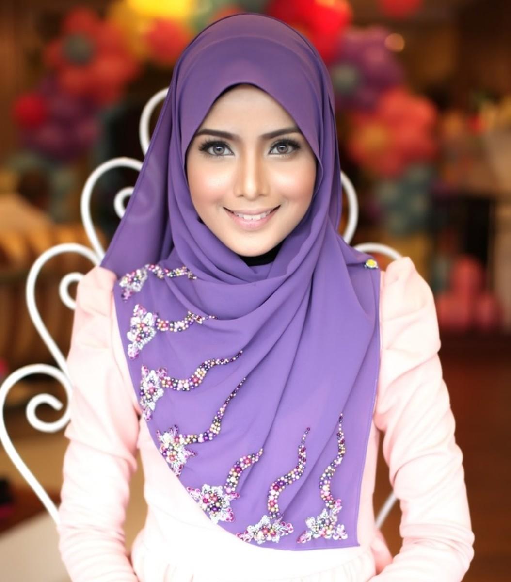 Purple hijab scarf worn covering her bosom