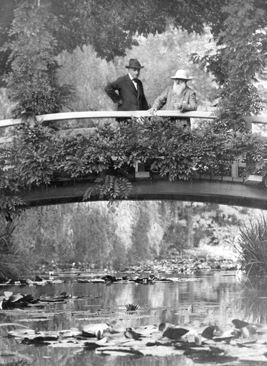 The elder Monet stands on his famous Japanese bridge with an unidentified visitor.