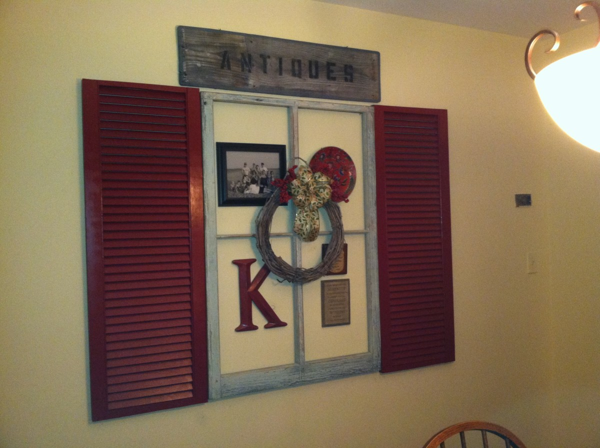 Wall grouping consist of free shutters, old window also free, decorator plate, large letter, wreath and ribbon all thrift or dollar store finds, family photo downloaded from phone enlarged and printed, $1 frame from dollar tree $10 all in!