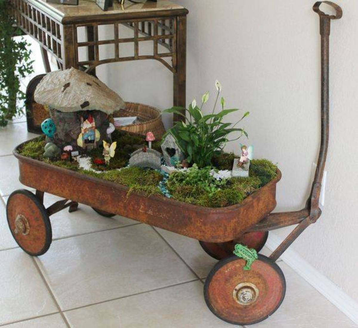 You need to drill holes in the bottom of the wagon if you are using outside where rain can overfill it. Inside, you can control the watering and can skip that step. Look at the use of one taller plant and then low moss for the garden.