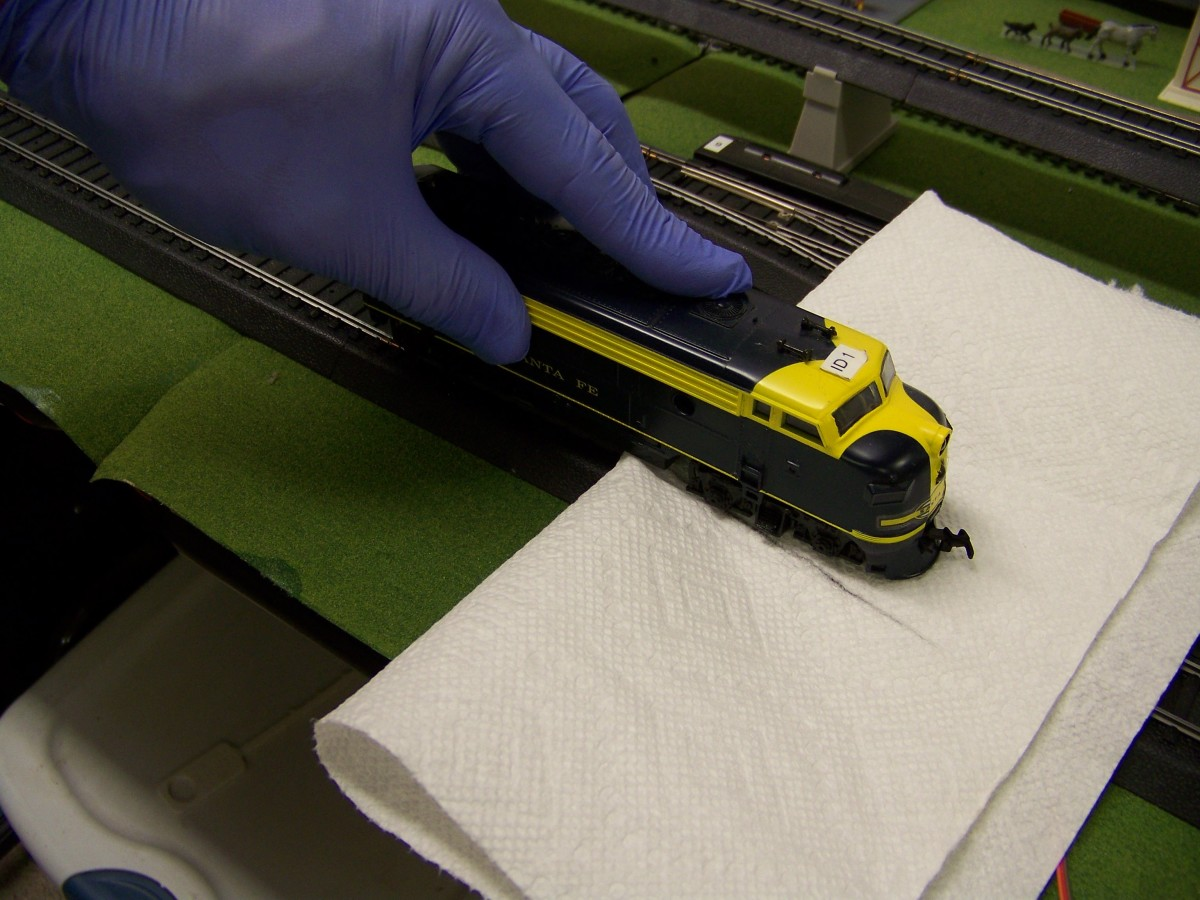 Cleaning the powered wheels of the locomotive can be achieved by turning on track power and touching the non-powered wheels to the track while the powered wheels rub against a paper towel.