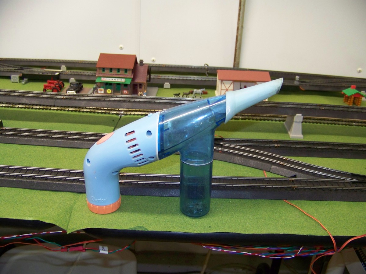 I use a small battery powered hand vacuum to remove debris from my layout. The nose of this vac is circular and small so it easily fits into small areas like between the rails.