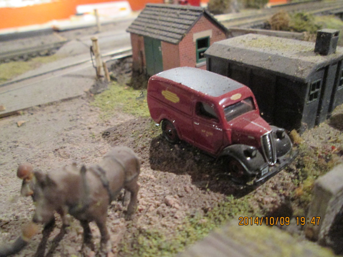 One of the light goods/parcels delivery vans stands in front of the concrete lineside hut (Ratio) with the brick stores shed (card kit, embossed plastic apex roof). A local farmer chats to the station master on his way home from ploughing
