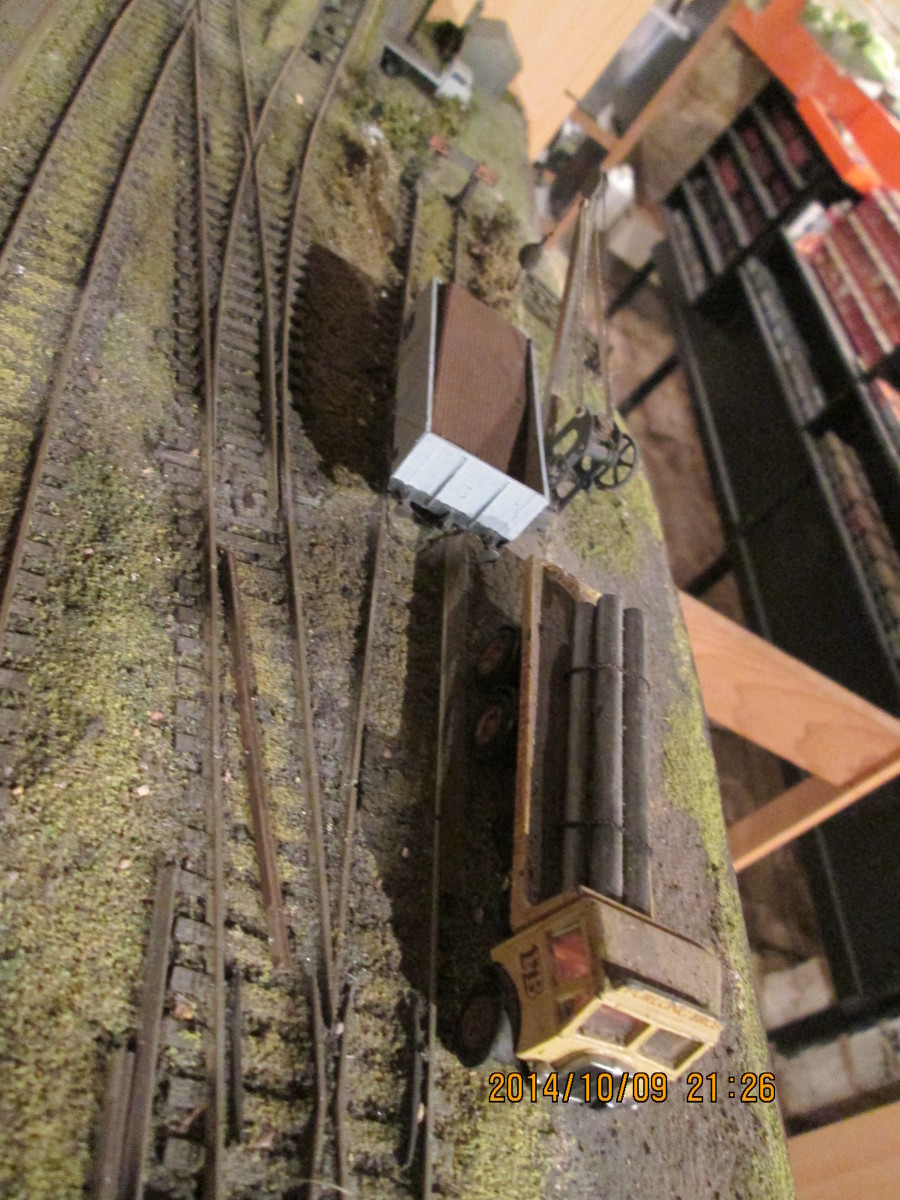 Looking down at the heavy lorry with pipe load (EFE Models' AEC Mammoth, Evergreen plastic tube ) by the crane by modified Parkside BR 13 ton open wagon (PC01A with unfitted wagon brakes replacing clasp brake sprue supplied) corrugated plastic 'load'