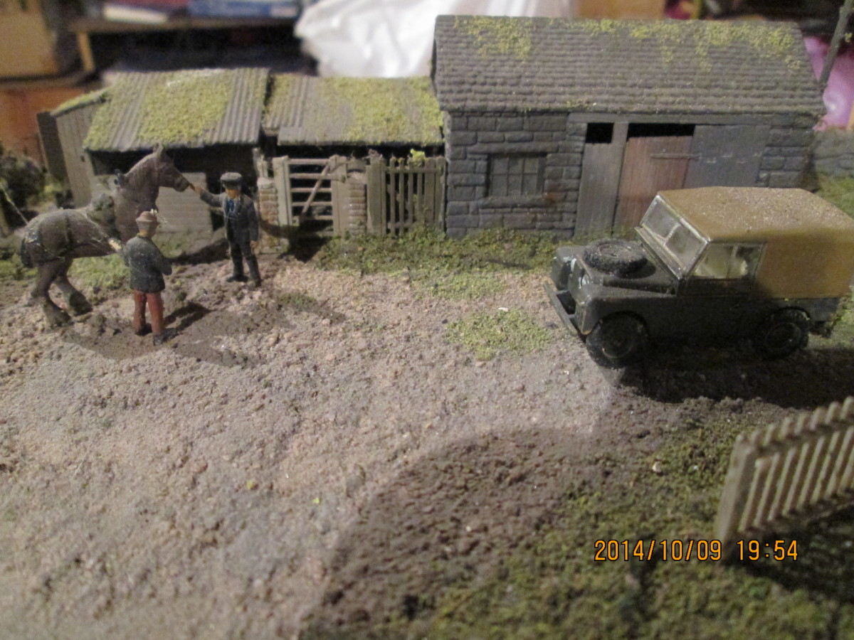 From left to right, privy, store shed pigsty, smithy - the farmer chatting to the stationmaster (left) and someone's Land Rover (Oxford Diecast) parked blocking the warehouse entrance