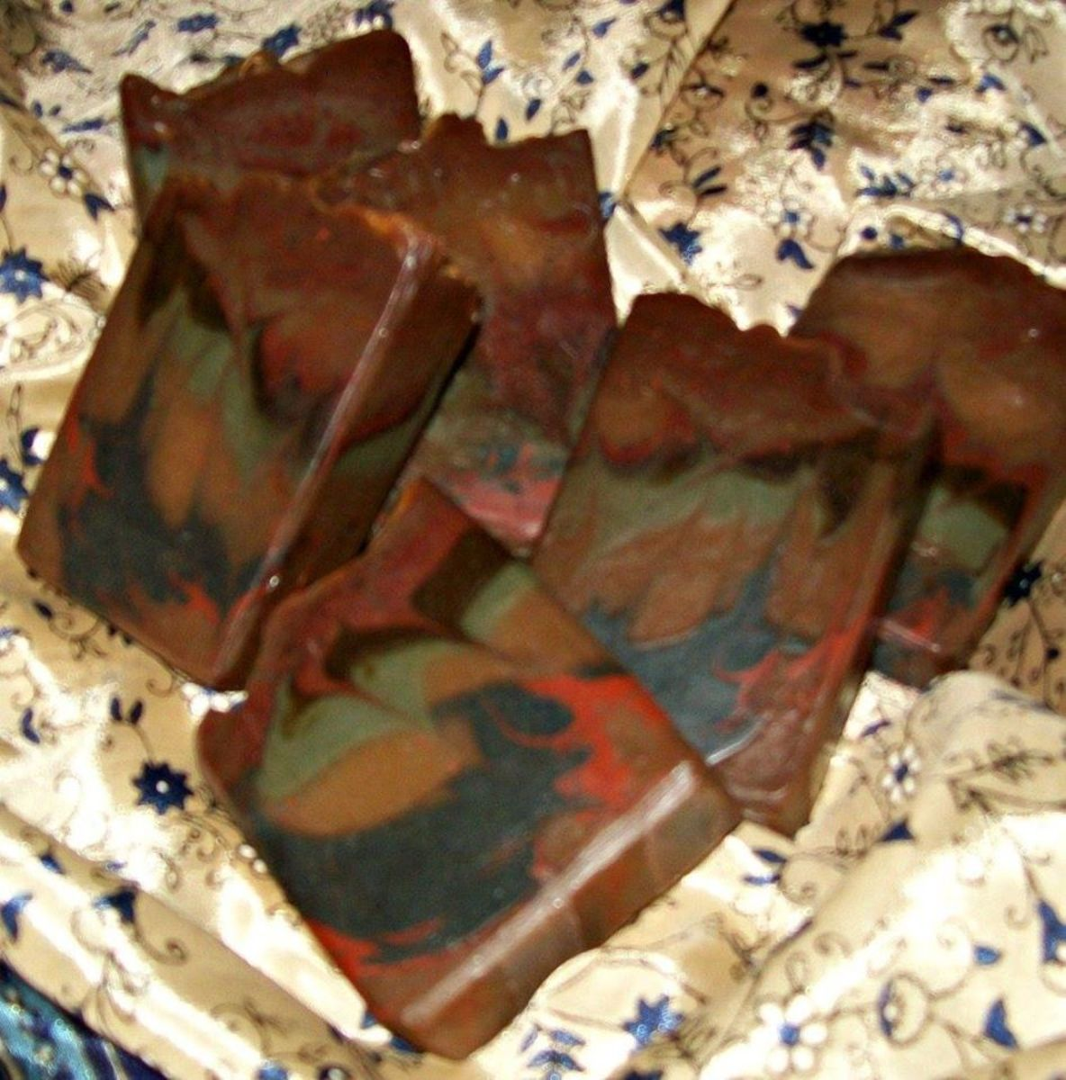 """Here is the same Bastile recipe scented with Nag Champa and with several colors of soap poured in layers, followed by a """"hanger swirl."""" This is a versatile recipe that colors and swirls beautifully."""
