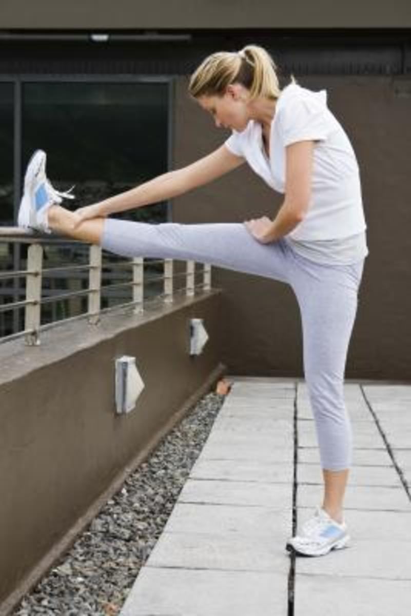 hamstring stretch using a low wall for assistance illustrated by a beautiful female in fitness/running gear