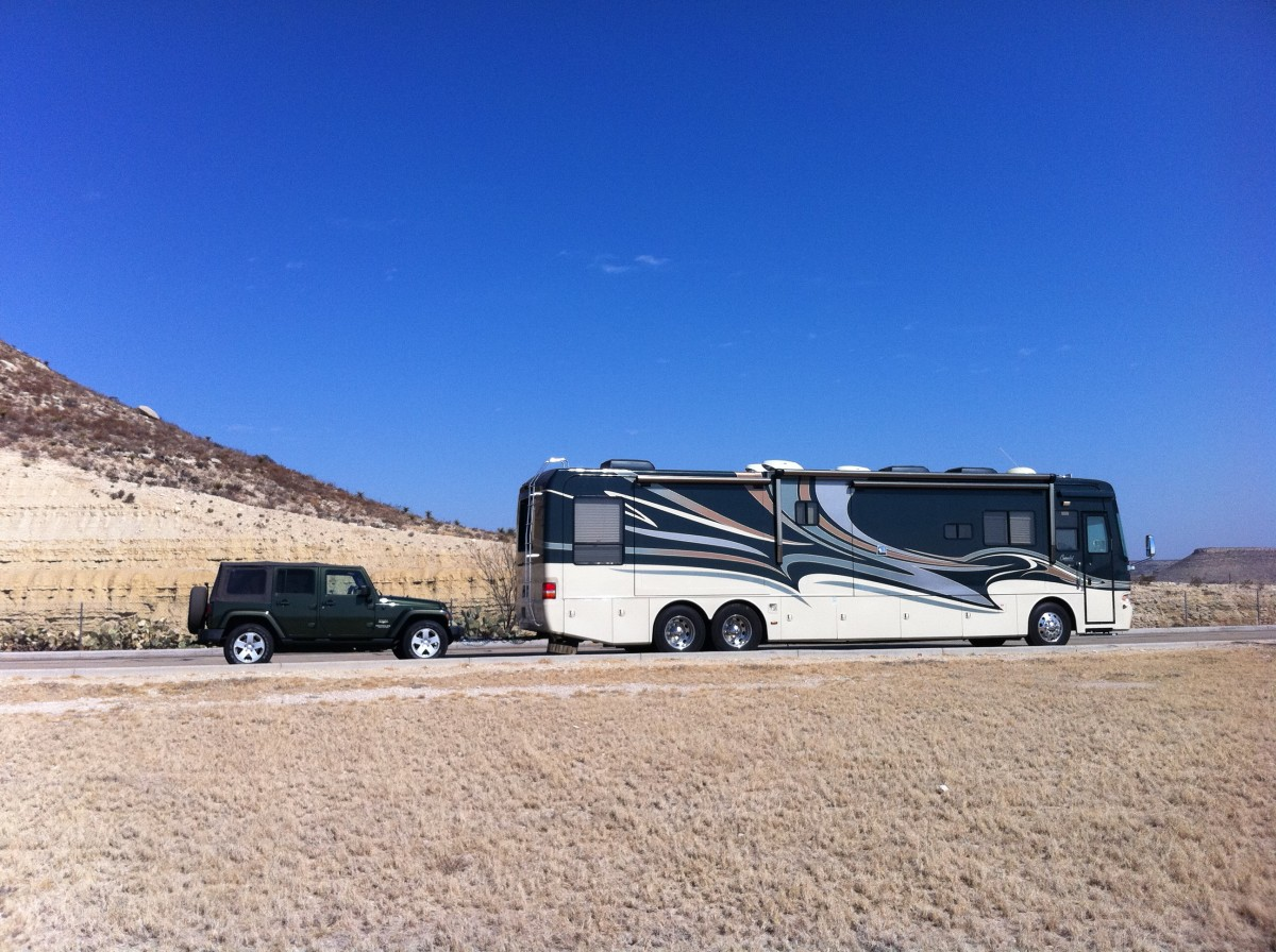 "A large motorhome pulling a Jeep tow car ""4-down"", which is a typical preferred towing configuration of most motorhome owners."