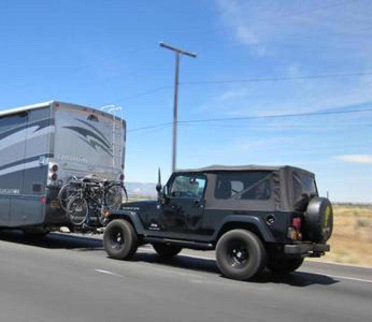 "RV towing a vehicle in the ""4-down"" mode, with all four wheels on the ground."