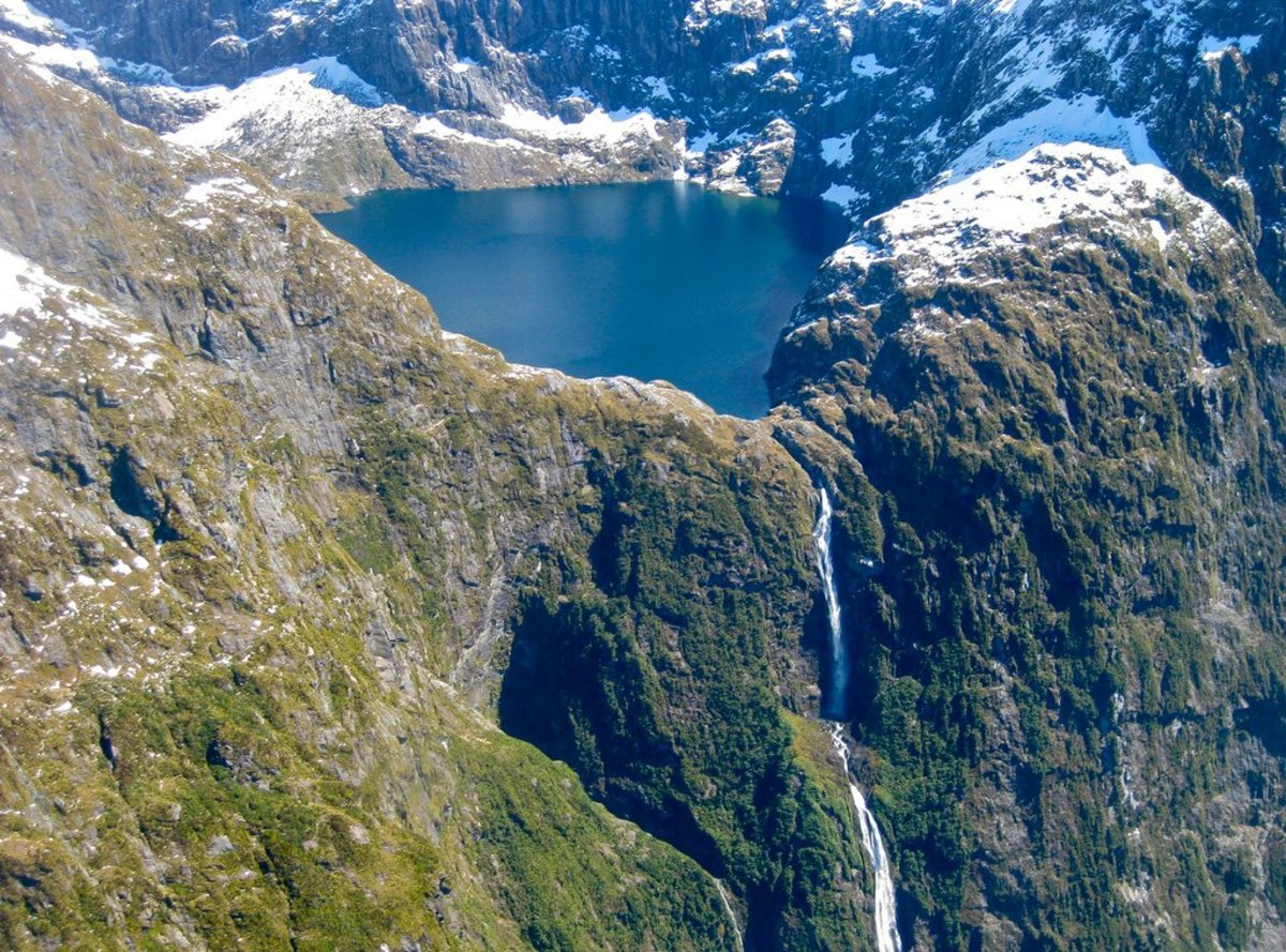 Browne Falls is located on a high mountain top in New Zealand. Because of its remoteness, Browne Falls is best viewed through a helicopter tour or boat tour or online.