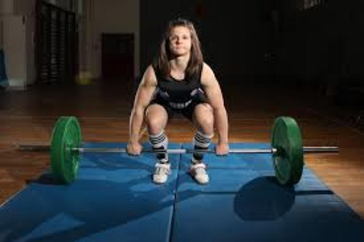 Girl beginning the deadlift phase of the clean.