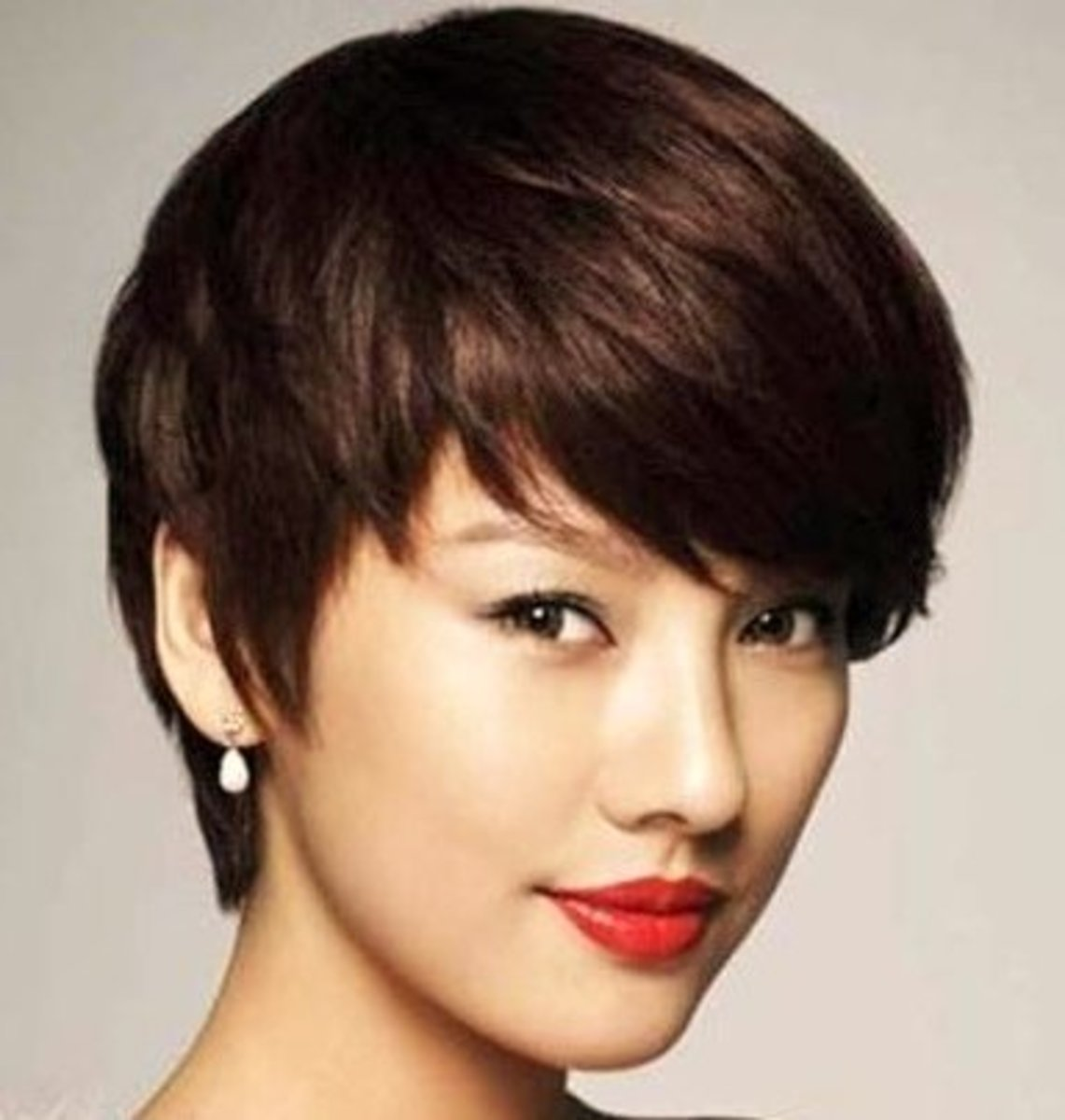 Asian pixie cut with long bangs. Great for full jaws.