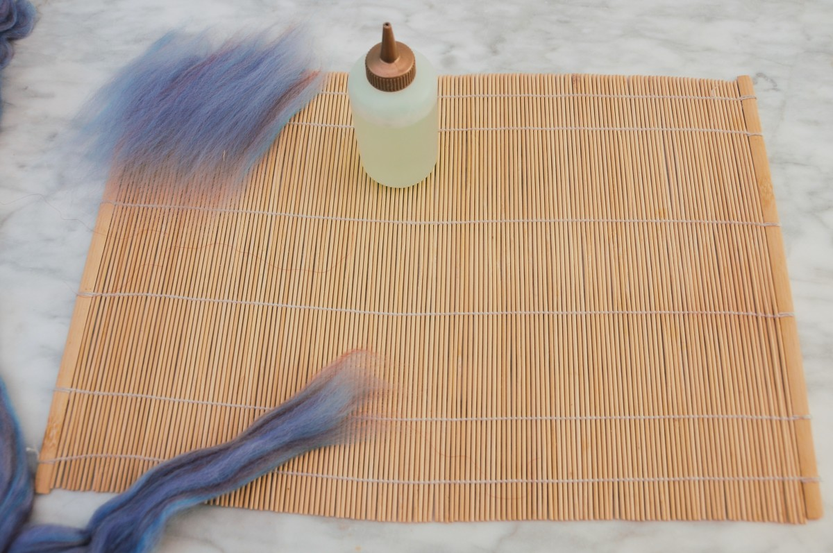 Begin by placing the woolen fibers down onto the sushi mat