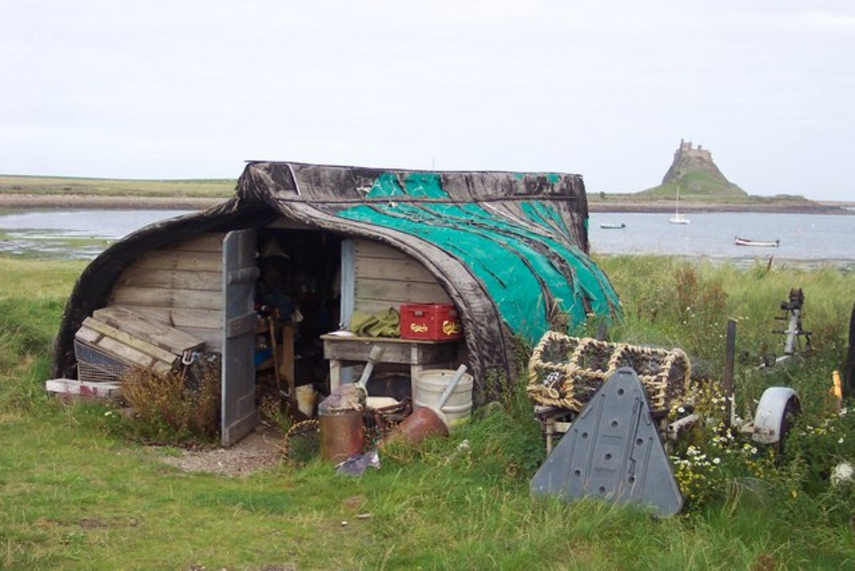 Fisherman's hut by the Ouse with view of Lindisfarne Castle. Several of these boat conversions along the edge of this small harbour on Holy Island.