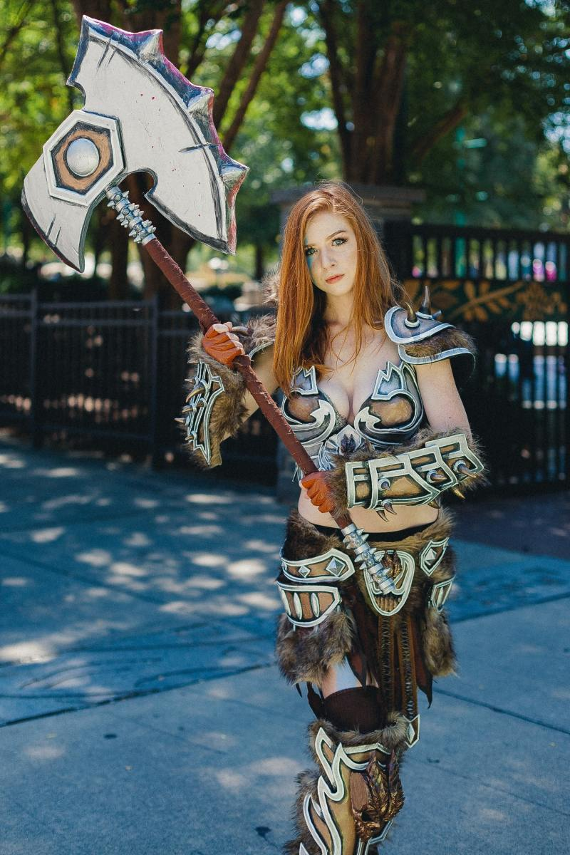 A woman wearing a cosplay costume and holding sword.