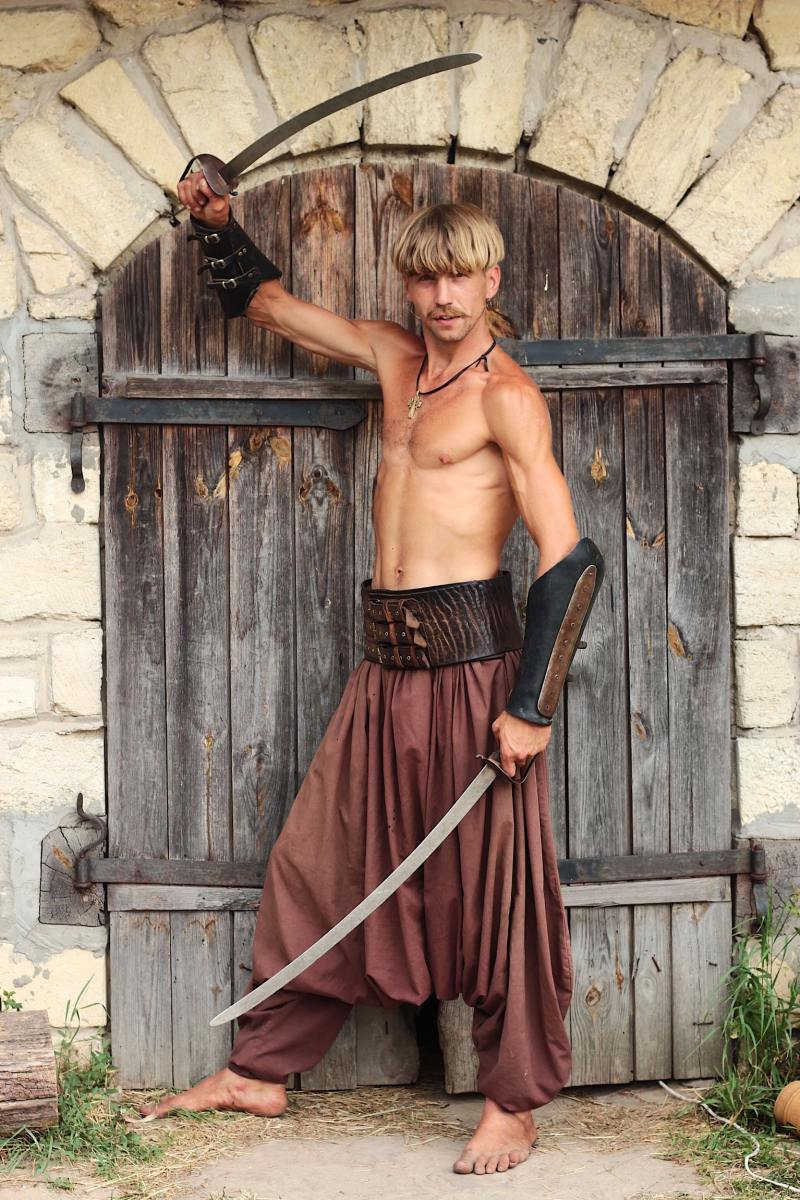 A man holding 2 swords while standing in front of a brown gate.