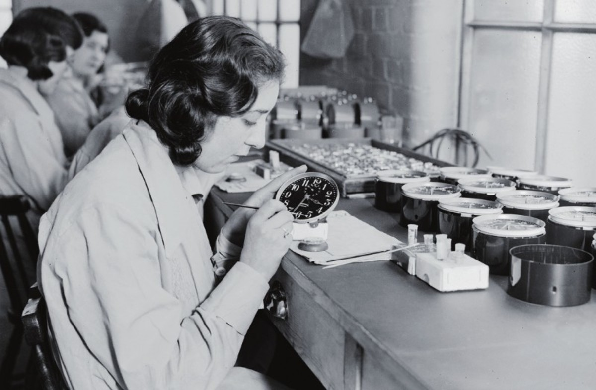 A radium girl painting clock dials in a factory.