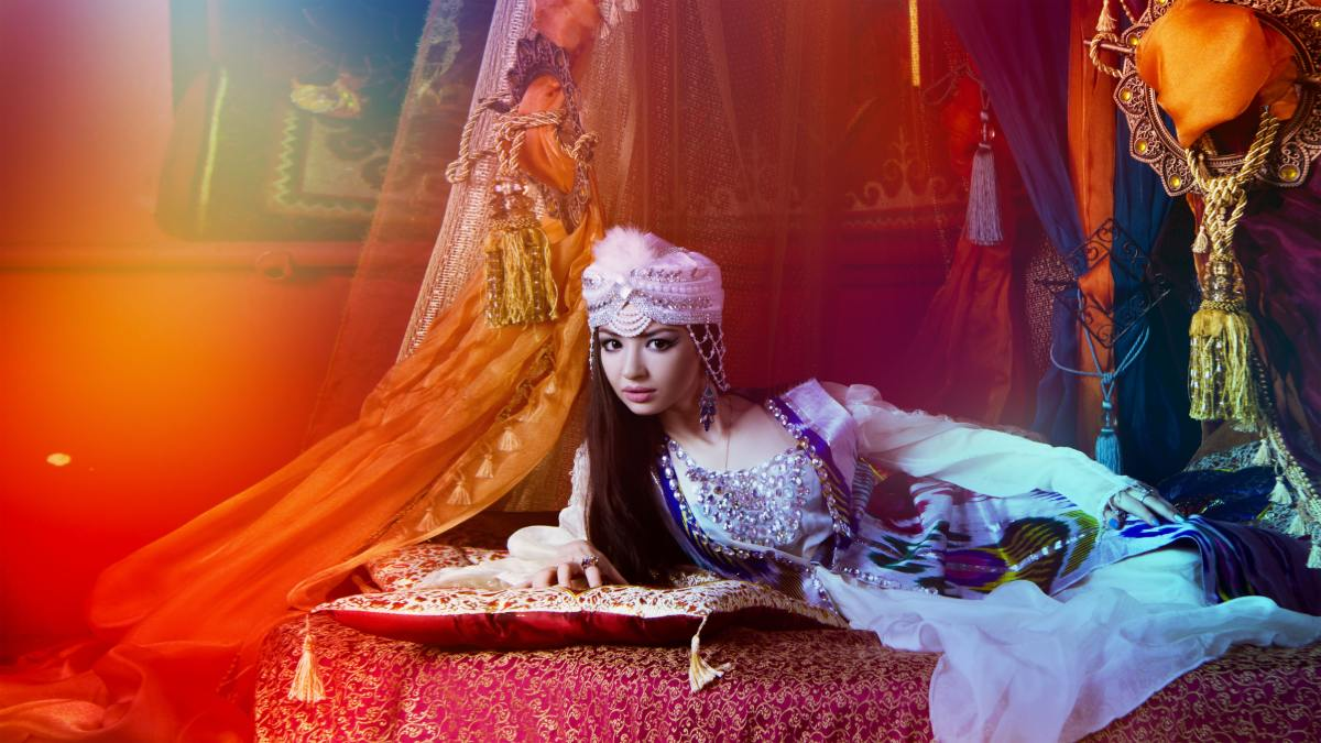 A woman reclines in a fantasy harem setting..